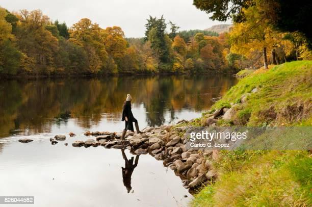 Asian girl wearing woolly walks on rocky edge of river
