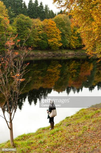 Asian girl wearing wooly hat standing beside calm river with colorful reflections