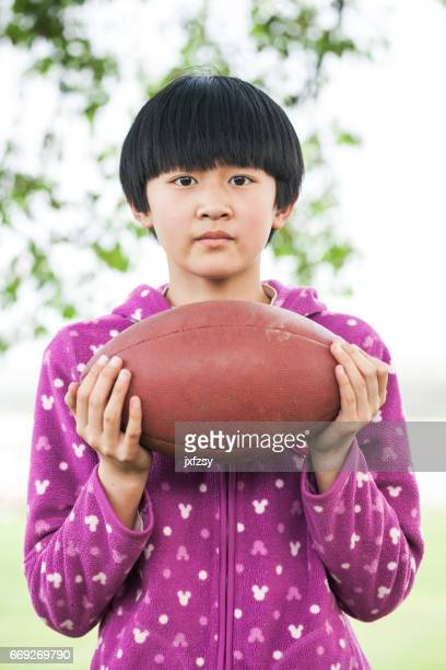 asian girl with football in green field
