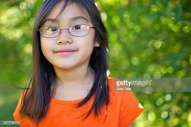 asian girl with glasses smiles in an orchard - オレンジ色のシャツ ストックフォトと画像