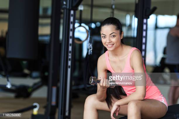 asian girl workout with dumbbells in fitness - canotta foto e immagini stock