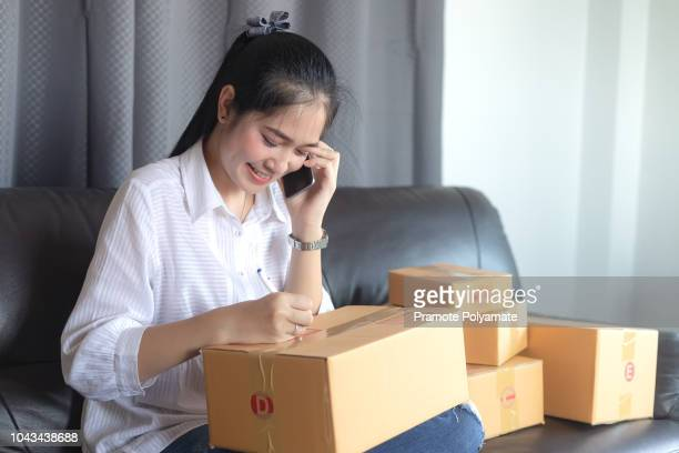 Asian girls get the order by phone, Online shopping young start small business in a cardboard box at work. The seller prepares the delivery box for the customer, online sales, or ecommerce.