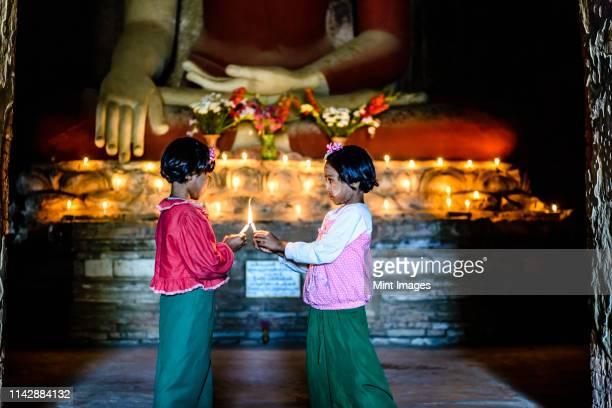 asian girls lighting candles in buddhist temple - fish love - fotografias e filmes do acervo