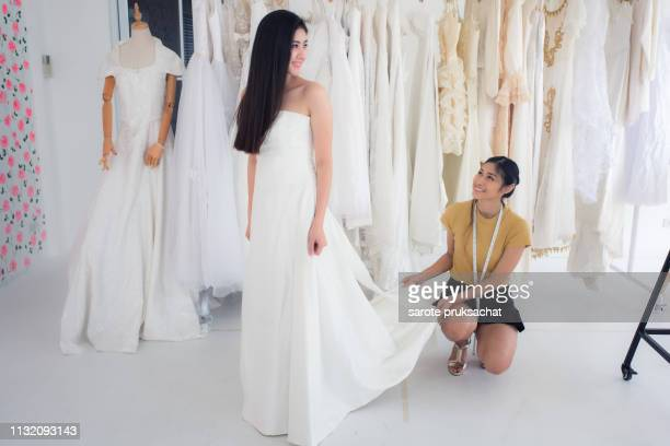 asian girls try wedding dresses and shop owners. - moment collection stock pictures, royalty-free photos & images