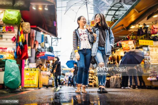 asian girls walking in a street market - taiwan stock pictures, royalty-free photos & images