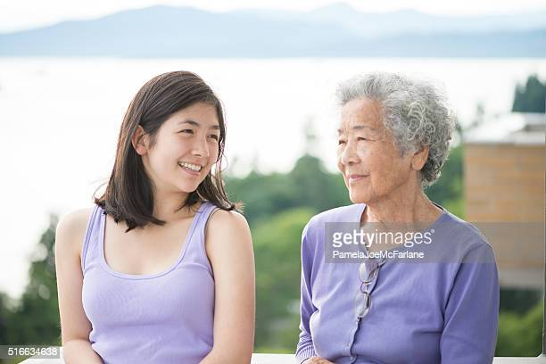 asian granddaughter and senior woman enjoying view from balcony, canada - chinese culture stock pictures, royalty-free photos & images