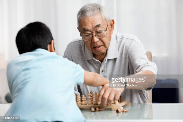 Asian grandfather and grandson playing chess