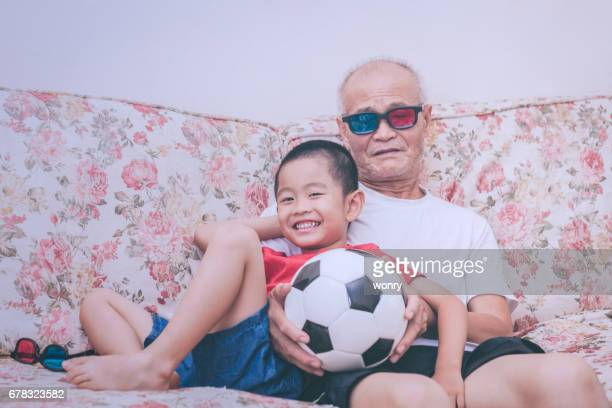 Asian grandfather and grandson playing with football