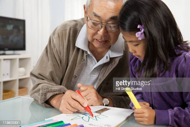 Asian grandfather drawing with granddaughter