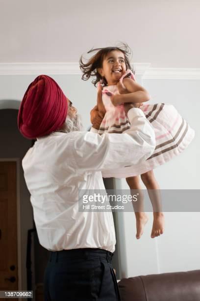 Asian grandfather lifting granddaughter