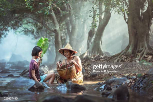 asian grandma and granddaughter catch crab in a basket in a stream in thailand, grandma teaches her granddaughter to survive. - niece stock pictures, royalty-free photos & images