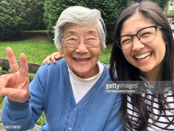 asian grandmother and eurasian granddaughter smiling for photo on bench - 90 plus years stock pictures, royalty-free photos & images
