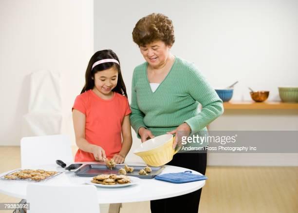 Asian grandmother and granddaughter making cookies