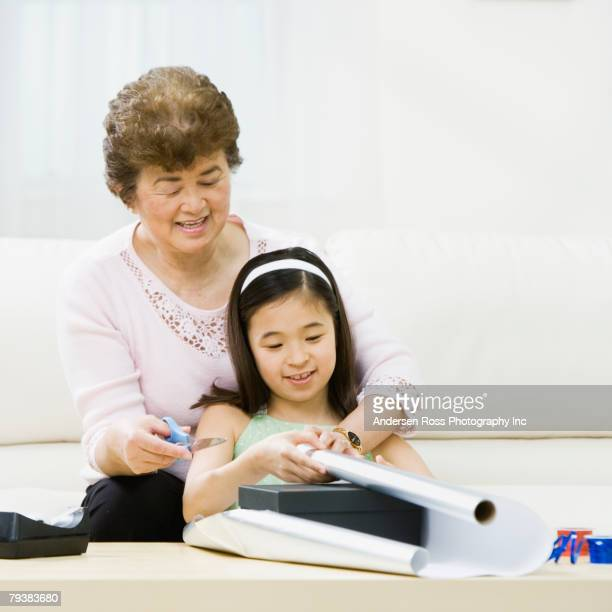 Asian grandmother and granddaughter wrapping gift