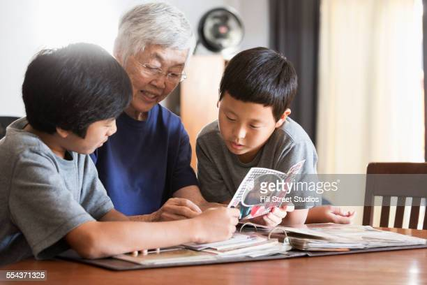 Asian grandmother and grandsons looking at photo album