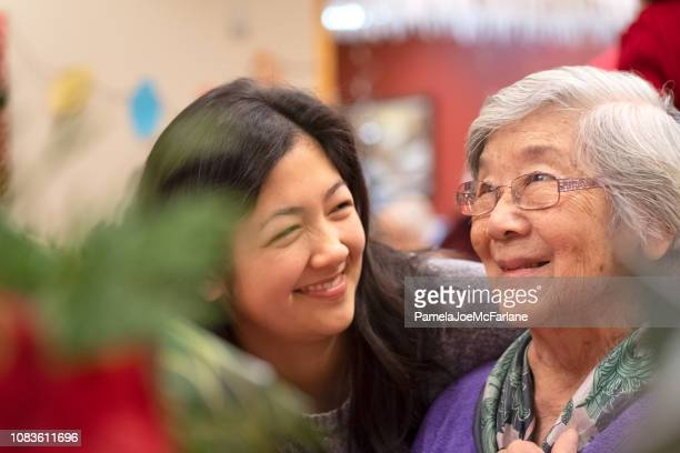 asian grandmother and mixed-ethnic granddaughter enjoying christmas celebration together - hygge stock pictures, royalty-free photos & images