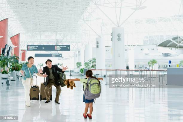 Asian grandparents greeting granddaughter in airport