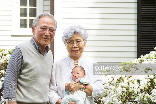 asian grandparents holding asian baby grandson - scarsdale stock photos and pictures