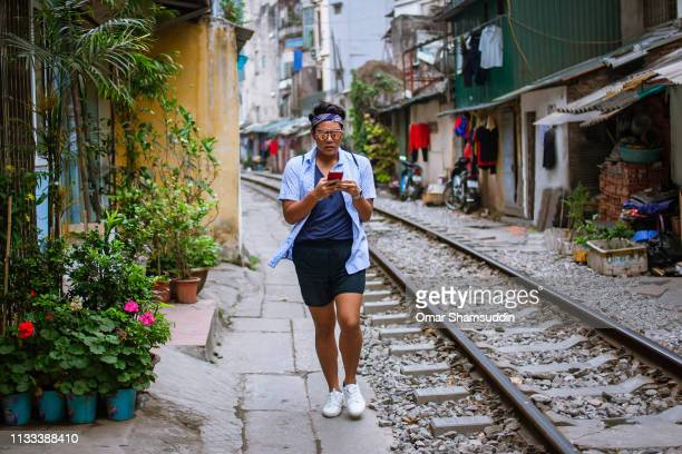 Asian guy walking by railroad track with smartphone in narrow alley in Hanoi