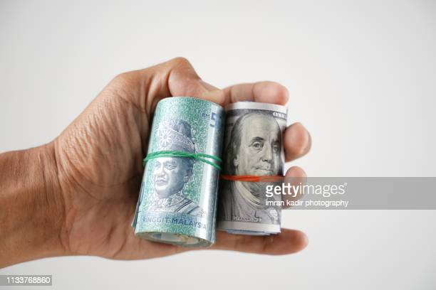 asian hand holding rolled dollar and malaysian ringgit - malaysian ringgit stock photos and pictures