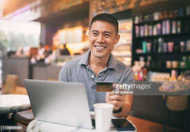 asian handsome man doing online payment using laptop in café - korean ethnicity stock pictures, royalty-free photos & images