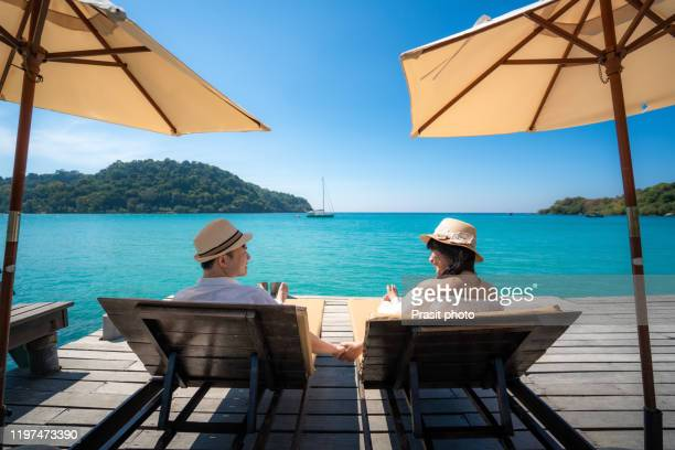 asian happy couple relaxing on chair beach with umbralla on wooden deck over sea background during summer vacation together in koh kood, trat, thailand. - ハネムーン ストックフォトと画像