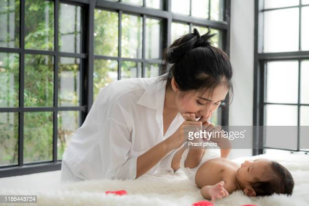 asian happy young mother kissing her two months old daughter's feet in bed at home - new stock pictures, royalty-free photos & images