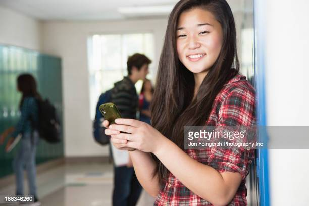 Asian high school student text messaging on cell phone
