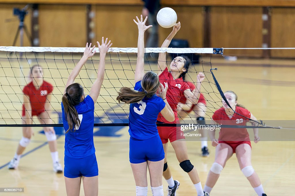 Asian high school volleyball player spikes volleyball against female opponents : Stock Photo