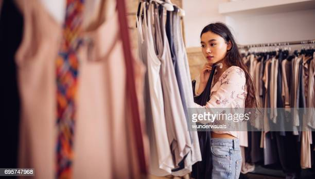 Asian hipster woman shopping for clothes inside a clothing store