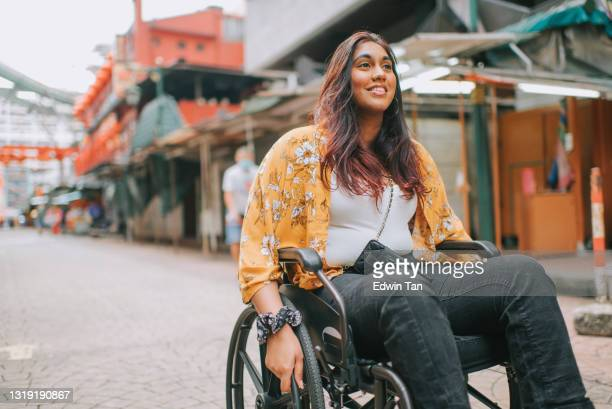 asian indian beautiful woman with disability using wheelchair exploring downtown district in kuala lumpur - tourist stock pictures, royalty-free photos & images