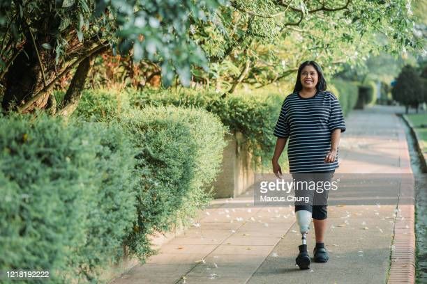 asian indian handicapped with prosthetic leg smiling woman jogging and exercising in the public park on sunny day - extra long stock pictures, royalty-free photos & images