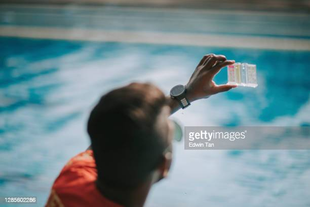 asian indian lifeguard pool testing kit being used in a swimming pool for water chlorine level - ph value stock pictures, royalty-free photos & images
