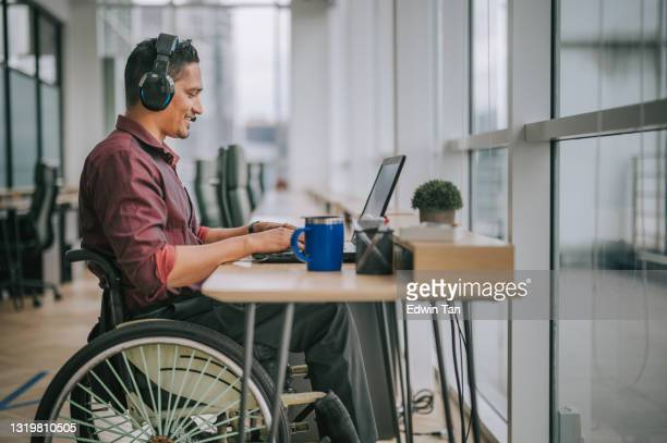 asian indian male white collar worker with disability on wheelchair talking to the camera video calling video conference with his business partners - employee stock pictures, royalty-free photos & images