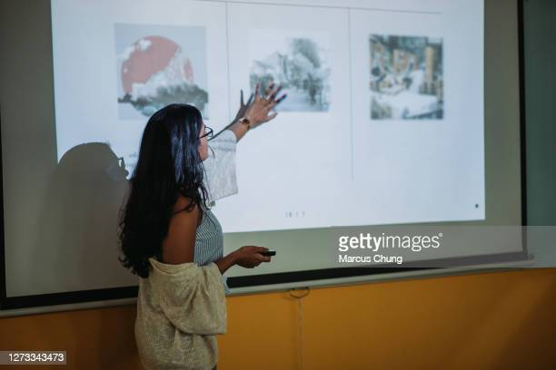 asian indian smiling female student presenting in college classroom - presenter stock pictures, royalty-free photos & images