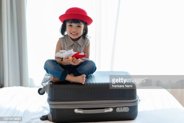 asian kid child girl playing with toy airplane. travel, tourism and tourist concept. - toddler at airport stock pictures, royalty-free photos & images