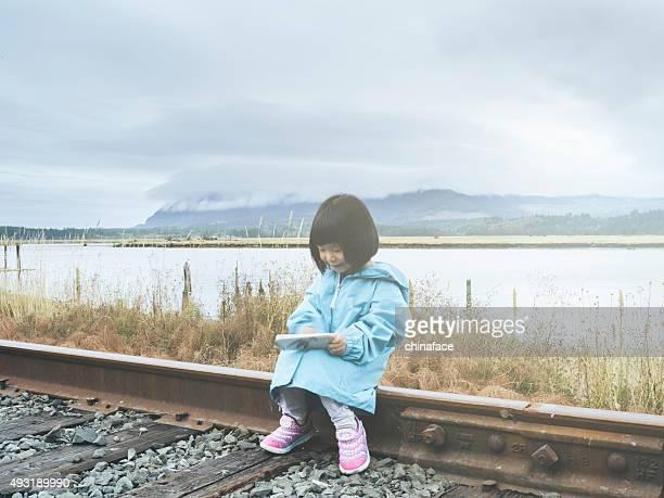 asian kid sitting on railway using cellphone