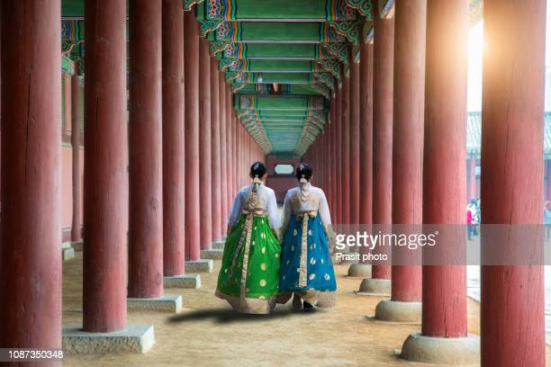 asian korean woman dressed hanbok in traditional dress walking in gyeongbokgung palace in seoul, south korea. - gyeongbokgung palace 個照片及圖片檔