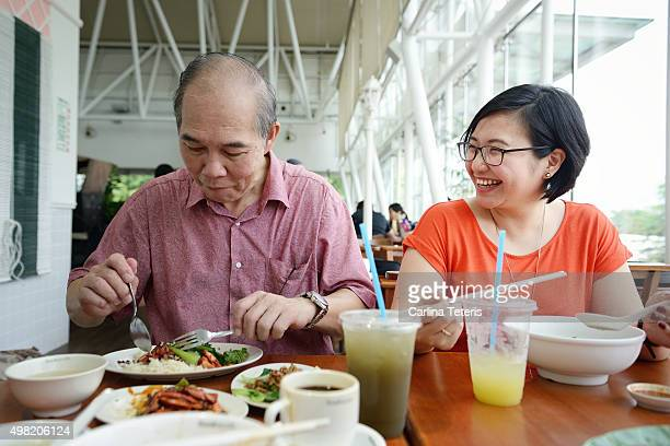 Asian lady and mature man having a meal together