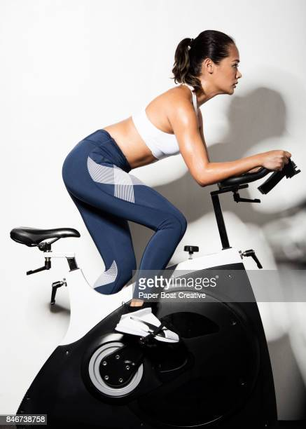 Asian lady in her ealy 30's working hard to go through her spinning class