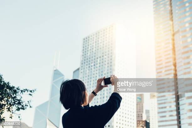 asian lady taking pictures of city buildings - fotohandy stock-fotos und bilder