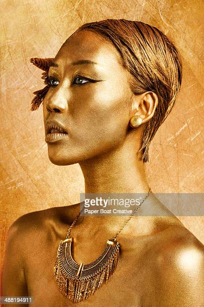 Asian lady with gold body paint on face and hair