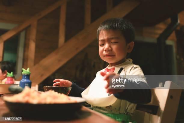 アジアの小さな男の子は食べるのが嫌いです - 喉が詰まる ストックフォトと画像