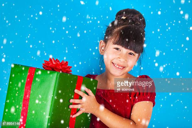 asian little girl holding big christmas gift box. - little girl giving head stock photos and pictures