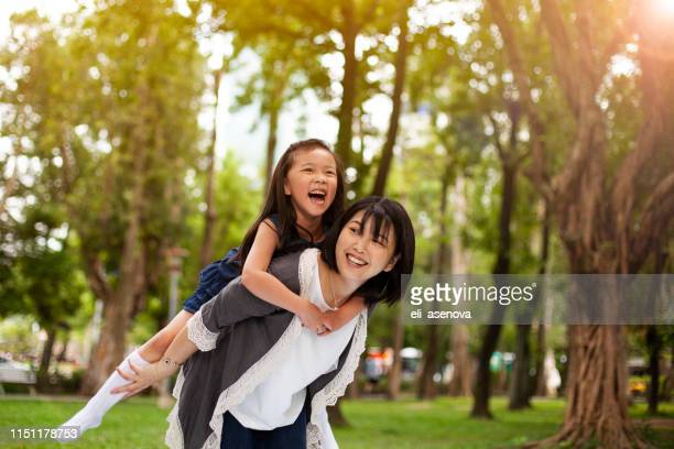 asian little girl on a piggy back ride with her mother in park taipei - vietnamese ethnicity stock pictures, royalty-free photos & images