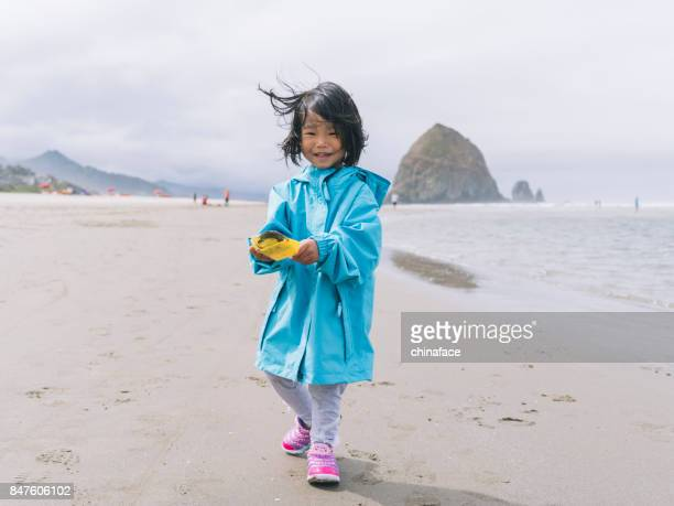 asian little girl playing at beach with toy shovel