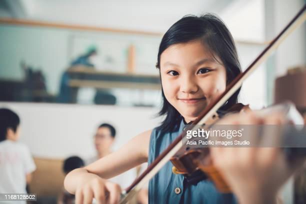 asiatische kleine mädchen spielen geige zu hause. - kunst, kultur und unterhaltung stock-fotos und bilder