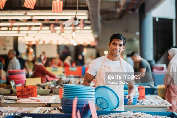 asian malay male stall owner standing at his fish stall and looking at camera with smiling face - market stall stock pictures, royalty-free photos & images
