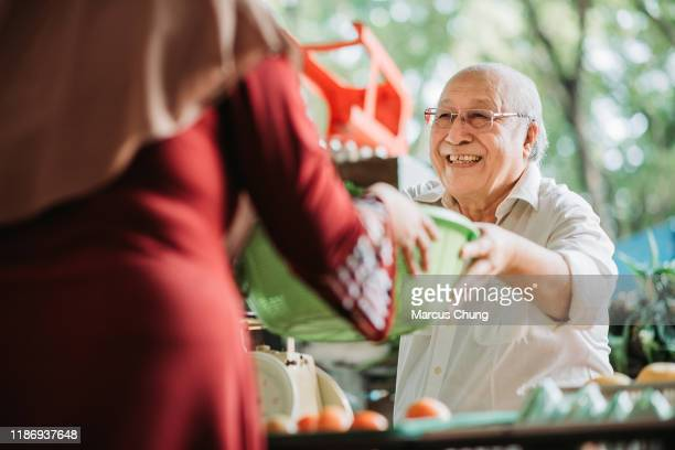 asian malay senior man vegetables stall owner receiving basket of vegetables from his customer for price calculation - malaysian culture stock pictures, royalty-free photos & images