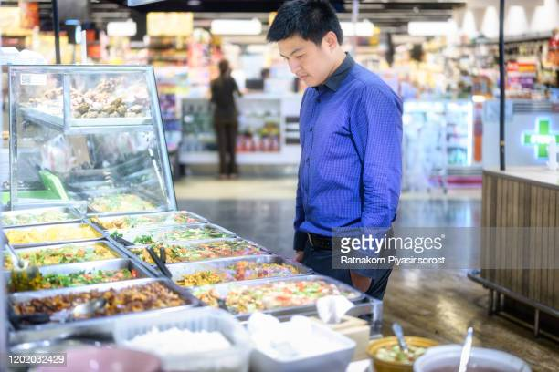 asian male buying a fast food for lunch in food court of supermarket in convenient store shop - singapore stock pictures, royalty-free photos & images